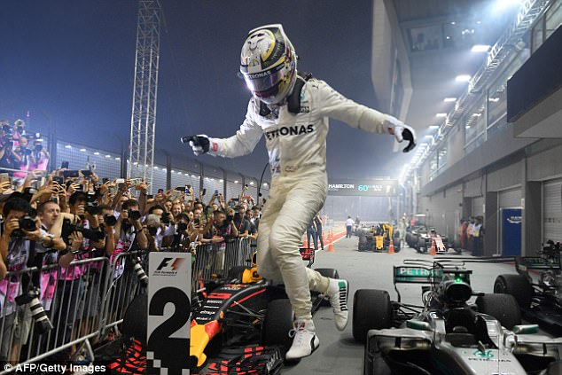 The Briton jumps off his Mercedes to celebrate with his team following his win on Sunday