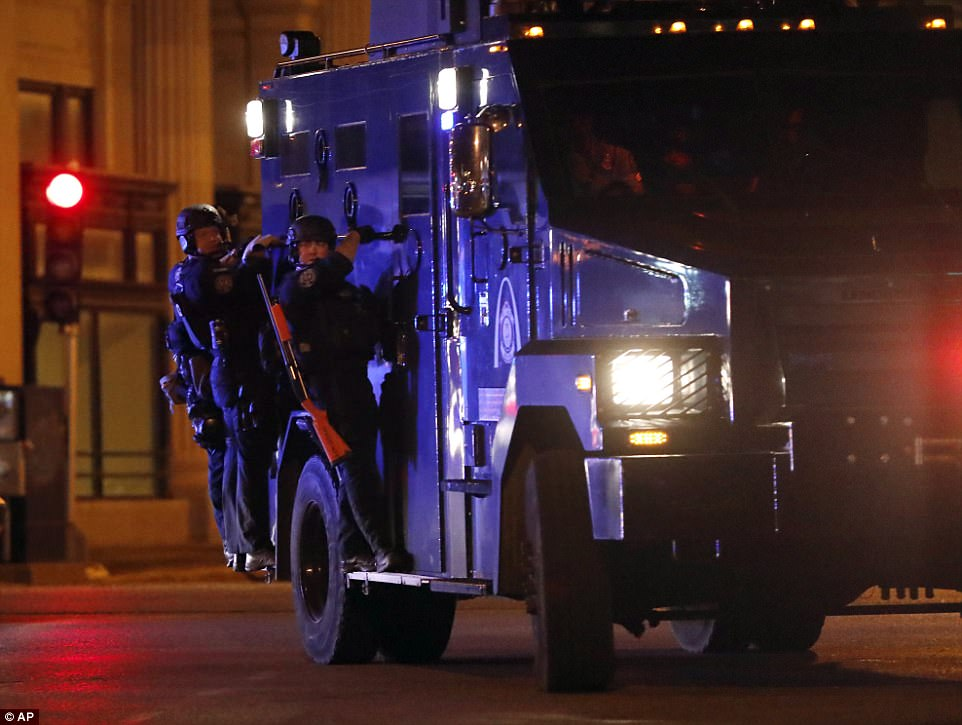 Cops arrive en masse to deal with protesters amid violence late at night in St Louis. Police later commended the daytime protesters for their responsible attitude - in stark contrast to the violence that came as night fell