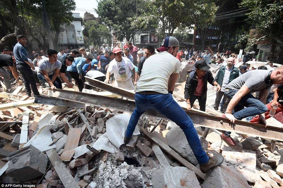 Locals are pictured clearing debris from the earthquake which left dozens of buildings collapsed - with metal and concrete sent falling to the ground