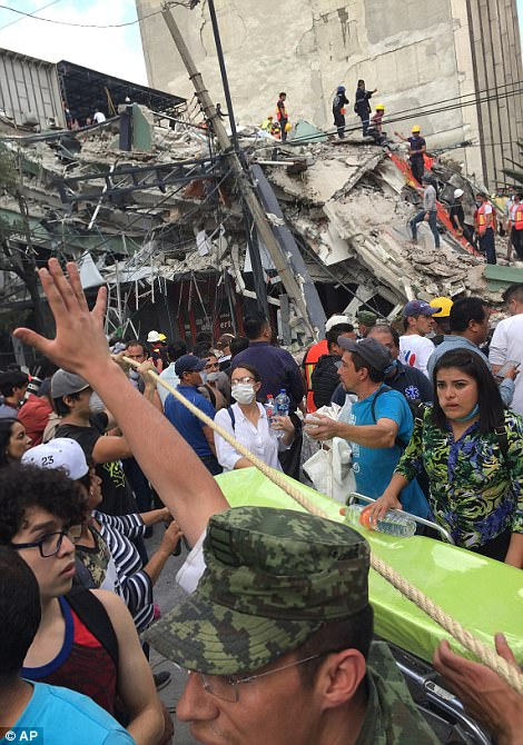 Volunteers and officials gather to help those trapped in a collapsed building