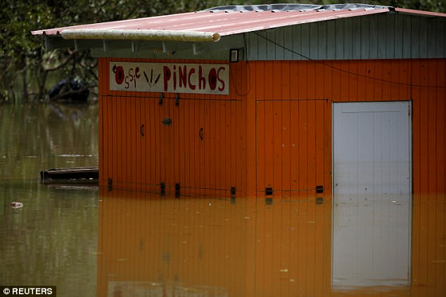 A restaurant submerged by flood waters is seen close to the dam of Lake Guajataca on Saturday
