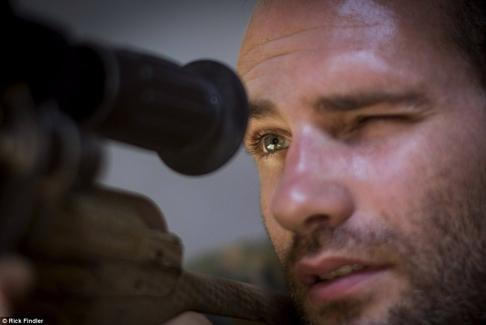 Macer looks through his sniper rifle's scope in Raqqa, Syria. Macer, who went to Kimbolton School in Huntingdon,  said his mere presence serves as a morale booster because it shows a British man cares about the people of Syria
