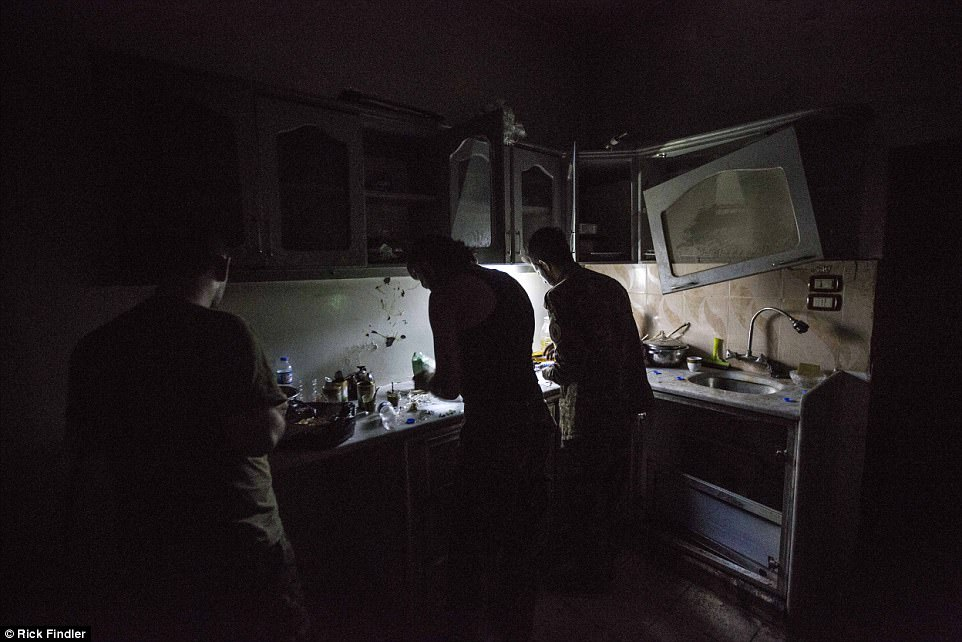 MFS soldiers cook a late dinner in the kitchen of an abandoned house on the front lines of Raqqa