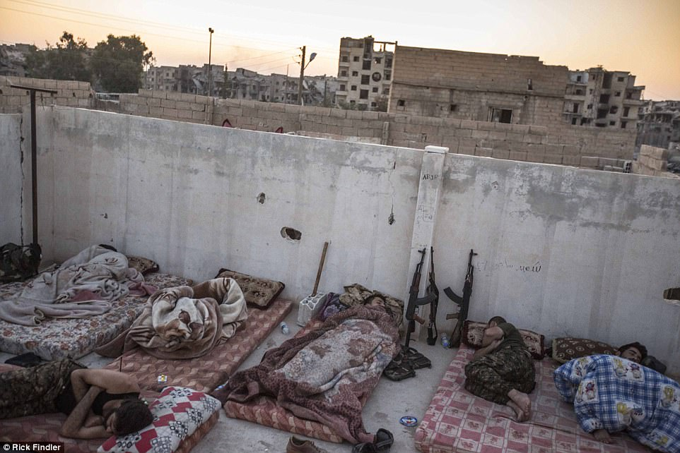 MFS soldiers sleep on the roof of their base as the sun rises in the early mornings on the front lines. They are at times just 300 feet away from ISIS - and constantly suffer from their mortar attacks and drones