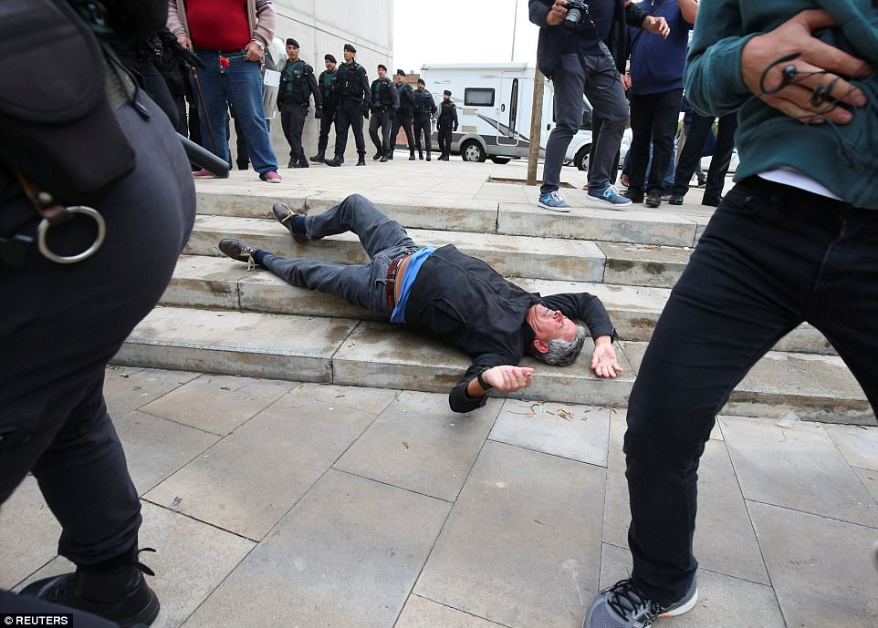 A man falls to the ground during scuffles with Spanish Civil Guard officers outside a polling station in Sant Julia de Ramis