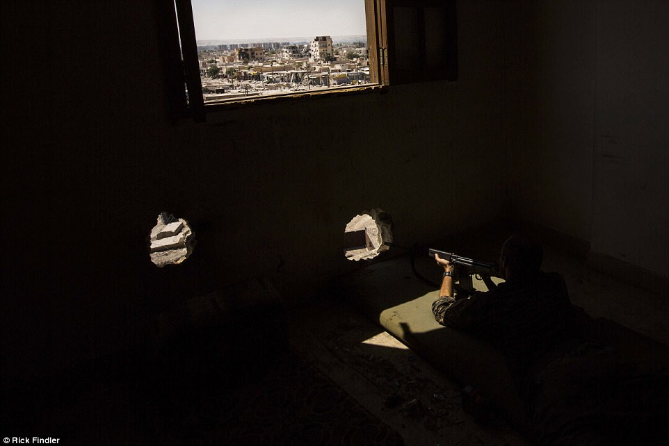 Macerwaits patiently as he looks out from a tower block in the search of ISIS militants