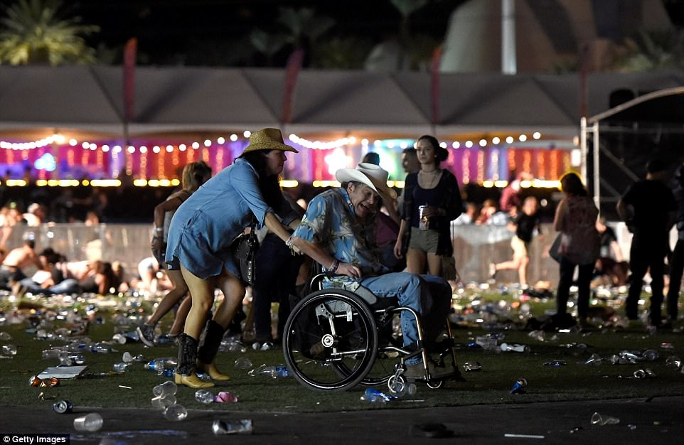 A man in a wheelchair, apparently in distress, is taken away from the festival in the wake of the shooting