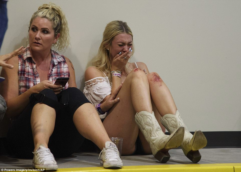 A woman cries while hiding inside the Sands Corporation plane hangar after the mass shooting on Sunday
