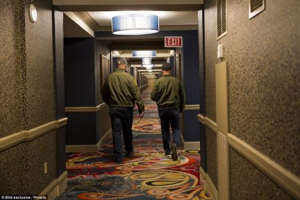Two investigators walk down the hallway, away from the scene