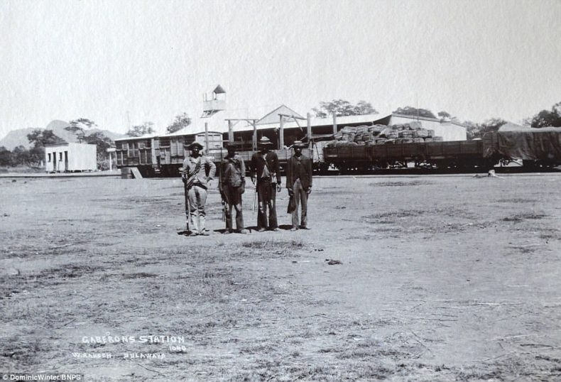 In this image troops armed with guns and bullets pose at the Gaberons Station in Bulawayo in front of a loaded train