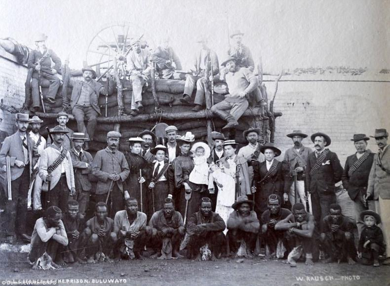 British troops and their civilian families pose alongside native African men in this photo taken at a military facility
