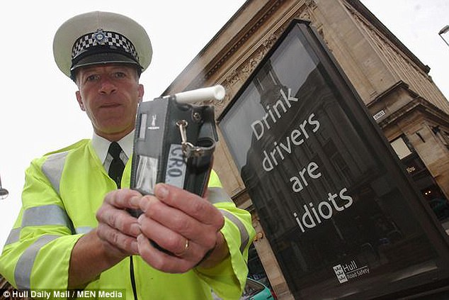 Former police officer and so-called 'road safety champion' Andy Walker once posed with a breathalyser in front of a sign saying 'Drink drivers are idiots' (pictured). He has been convicted of drink-driving - for the second time