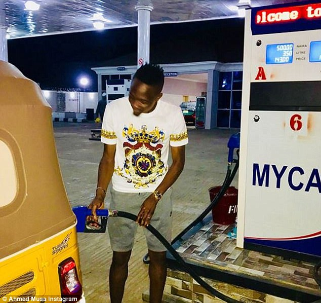Ahmed Musa fills up a car with petrol as he poses at the station which is now owned by him