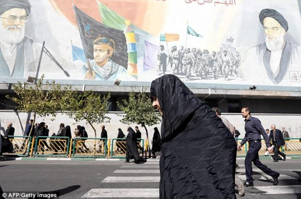 An Iranian woman walks past pictures of Iranian supreme leader Ayatollah Ali Khamenei (top L) and of late Iranian supreme leader Ayatollah Ruhollah Khomeini (top R). Trump's speech from the White House will address an array of Iran's troubling non-nuclear activities, officials have said
