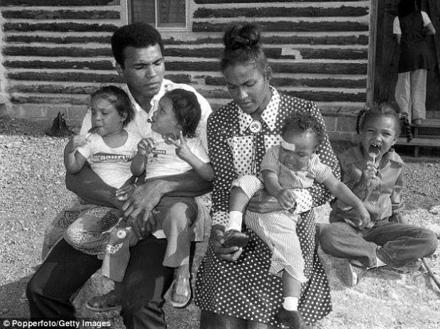 Former heavyweight champion Muhammad Ali is pictured with his wife Belinda and their four children. He holds 3-year-old twin daughters Reeshemah (left) and Jamillah while 1-year-old Muhamman sits on his Mother's knee. Their daughter Laila, 5, licks on a lollipop at Deer Lake, Pennsylvania