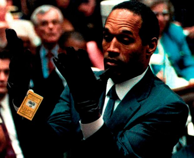 OJ Simpson tries on gloves during his murder trial in 1994. He was ultimately acquitted