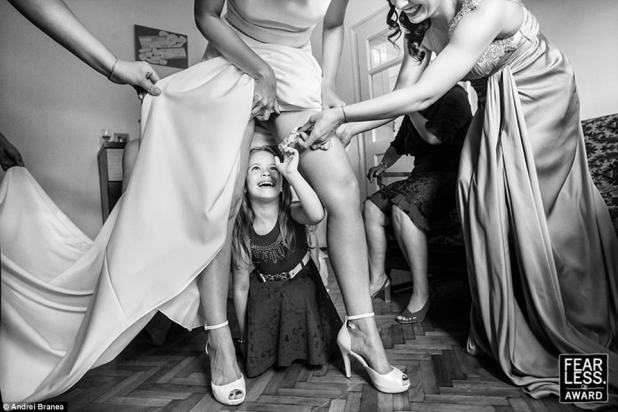 Going for the garter:Andrei Branea of Romania captured this darling image of a little girl crawling under a bride's dress