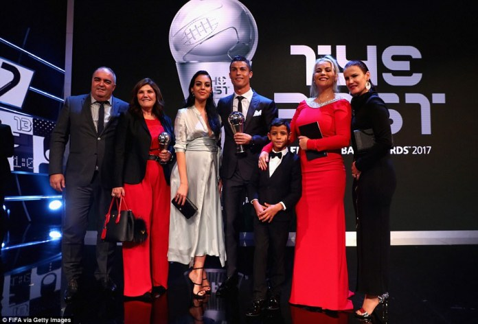 Ronaldo is photographed on stage alongside friends and family after retaining his crown ahead of Messi and Neymar