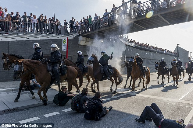 Mounted policemen ride through a group of protesters sitting on the ground, in Hamburg, Germany, during the G20 Summit in July