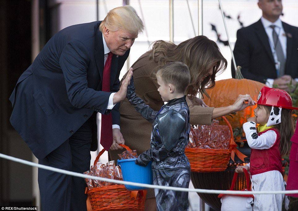 President Donald Trump gives a young boy a high five as he and First Lady Melania give out treats at the White House