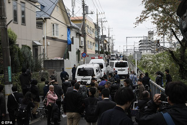 Grisly find: Police investigators guard an apartment building (centre, blue sheet) as members of the media crowd around in Zama, Kanagawa Prefecture, Japan