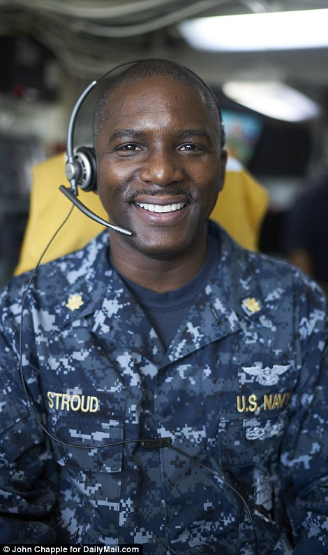 All hands on deck: One of the most important man on the flight deck is Lieutenant Commander Erick Stroud (pictured) who serves as the Aircraft Handling Officer (ACHO) - also called the handler or mangler and manages the movement and positioning of aircraft