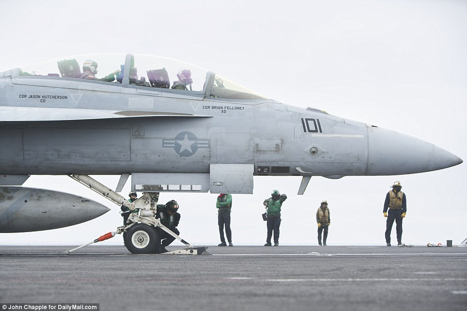 The flight deck is awash with dedicated crewmen wearing different colored jerseys.Green jerseys (center) operate the jet blast deflectors, and aircraft handlers wear yellow jerseys (right)