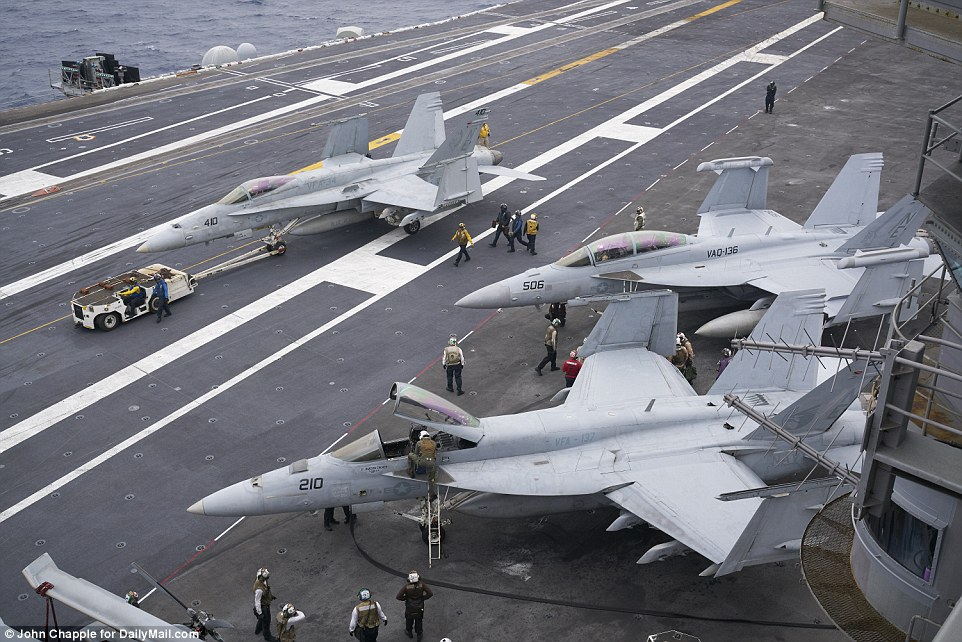 Four giant elevators brought aircraft up from the hangar deep below the 4.5 acre flight deck as Super Hornets lined up on deck to be catapulted into the air - just like in a real war