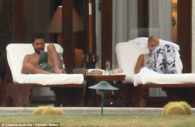 How romantic: Sofia appeared to peek over boyfriend Scott's shoulder before sitting down on a lounger next to him