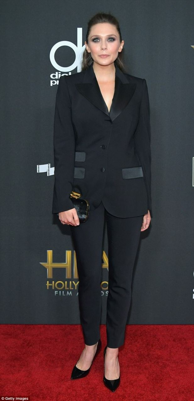 On trend: Elizabeth Olsen, 28, looked slender in a tuxedo pantsuit and went for a dramatic look with heavily lined eyes and smoky shadow on the lids