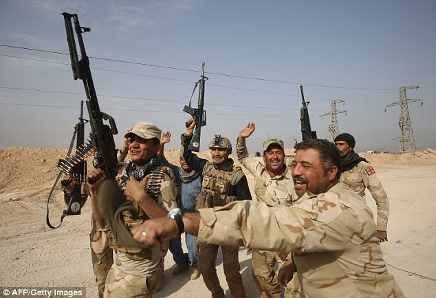 Iraqi forces dance on November 4, 2017 near the Syrian border after recapturing the border town of Qaim