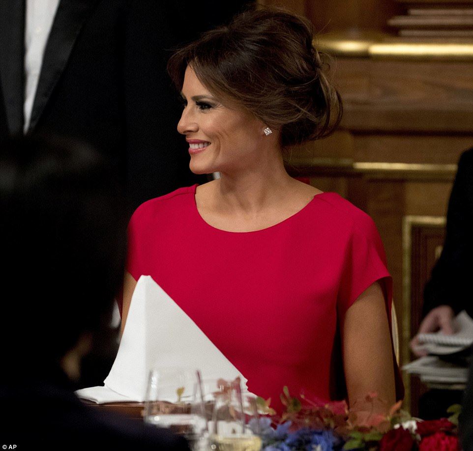 Glamorous: The first lady, 47, donned a bright red, floor-length gown with short sleeves on the occasion, wearing little jewelry for the event, which was hosted by Japanese Prime Minister Shinzo Abe at the Akasaka Palace