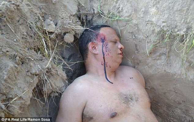 The 50-year-old boxing coach released dramatic photographs of his 'blood-stained corpse'