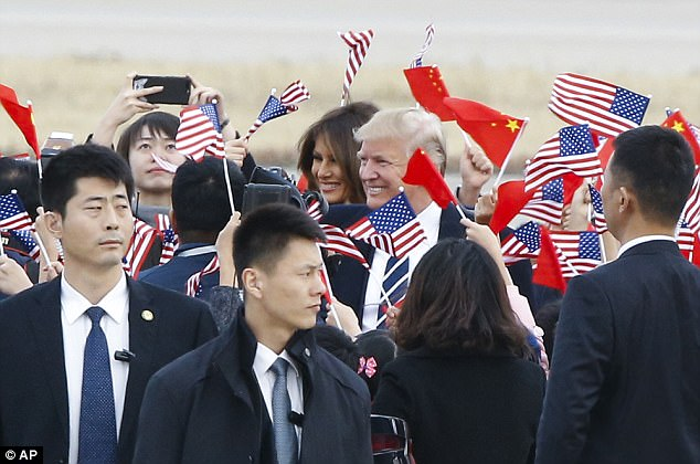 Children waving American flags greet the Trumps as they arrive at the Beijing airport