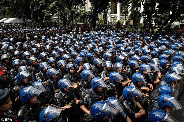 Riot police gather for a briefing ahead of a protest near the US embassy in Manila