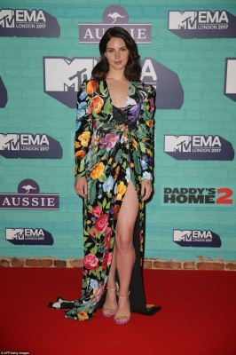 Flower power: Lana brought her chic glamour to the event, ensuring the show off her curves in a skin-tight floral plunging number, which showed off her toned legs