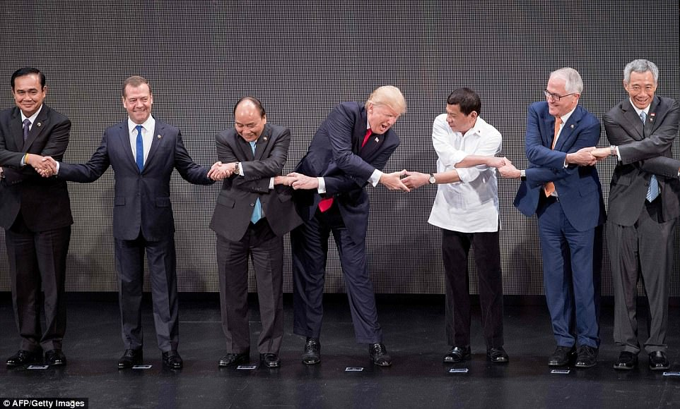 AMERICA! NUMBER ONE! Ultimately Trump figured out that he had to cross his arms and connect with the group – but Russian Prime Minister Dmitry Medvedev (2nd left) decided not to participate and kept his arms wide open
