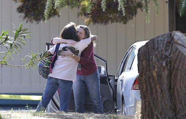 The California gunman who killed at least four people and hospitalized ten others was identified on Tuesday as Kevin Janson Neal, 43. Pictured above, women embrace outside Rancho Tehama Elementary, where Neal opened fire