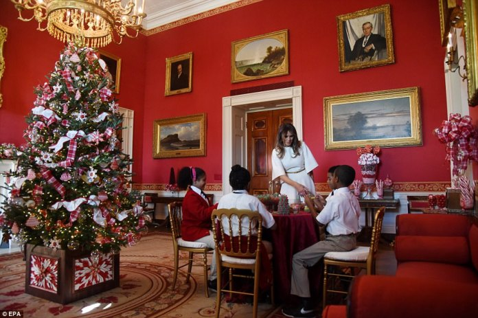 In the Red Room, decorated with sweets, Melania Trump helped a quartet of youngsters make gum drop trees, while warning them about all the sugar