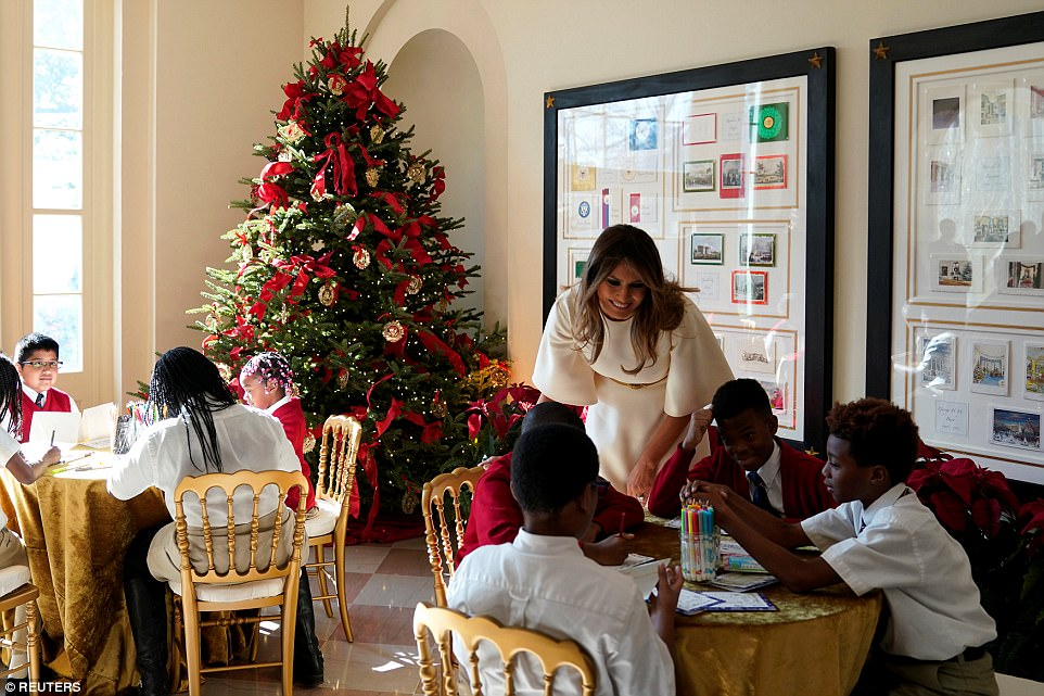 Melania Trump leans over to assess how the Christmas card decorating is going in the 'Bookseller's' area of the White House's East Wing. That part of the tour featured vintage holiday cards from past administrations