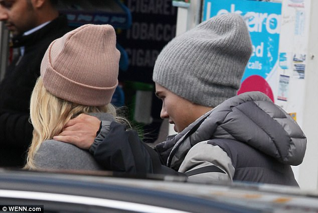 Hands on: Mollie was ready for action beneath her heavy coat as she sported skin-tight gym leggings and trainers while peeling on a grey overcoat with a waist-defining tie and a pink beanie with her hair falling from underneath