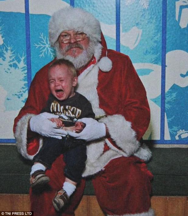 ¡Bájame!  Este niño pequeño está rojo en la cara por gritar tanto dentro de la gruta festiva