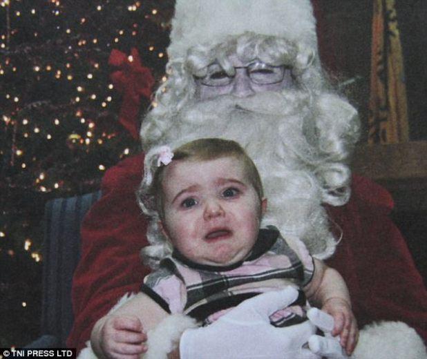 Aterrorizado: una niña pequeña parece asustada por Papá Noel, quien tiene una cara espeluznantemente blanca