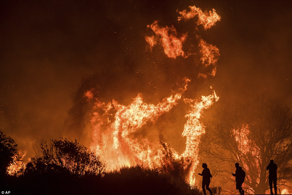Motorists on Highway 101 watch flames from the Thomas Fire leap above the roadway north of Ventura, California, on Wednesday.As many as five fires have closed highways, schools and museums, shut down production of TV series and cast a hazardous haze over the region