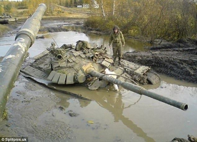 Right muddy mess: A tank driver is spotted surveying the mess he's gotten himself into this time. Standing on top of his vehicle, the cadet has realized he may be hitchhiking back to base