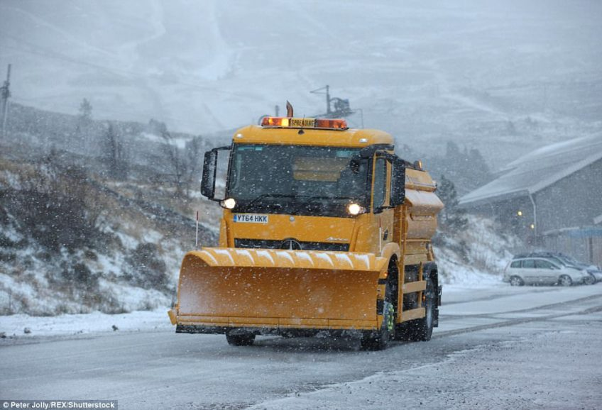 A snowplough in a blizzard in the Cairngorm National park.A yellow 'be aware' warning is in force for the southern half of Scotland