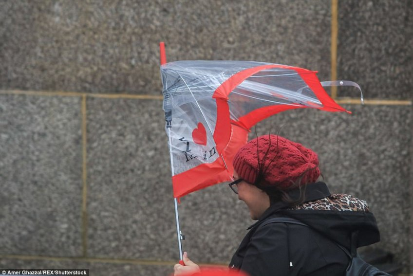 Pedestrians were caught in the strong winds and heavy rain on Westminster Bridge in London
