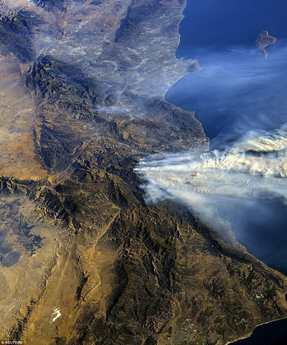 The photos were posted on Twitter by astronaut Randy Bresnik, who wrote: 'I was asked this evening if we can see the SoCal fires from space. Yes Faith, unfortunately we can. May the Santa Anas die down soon'