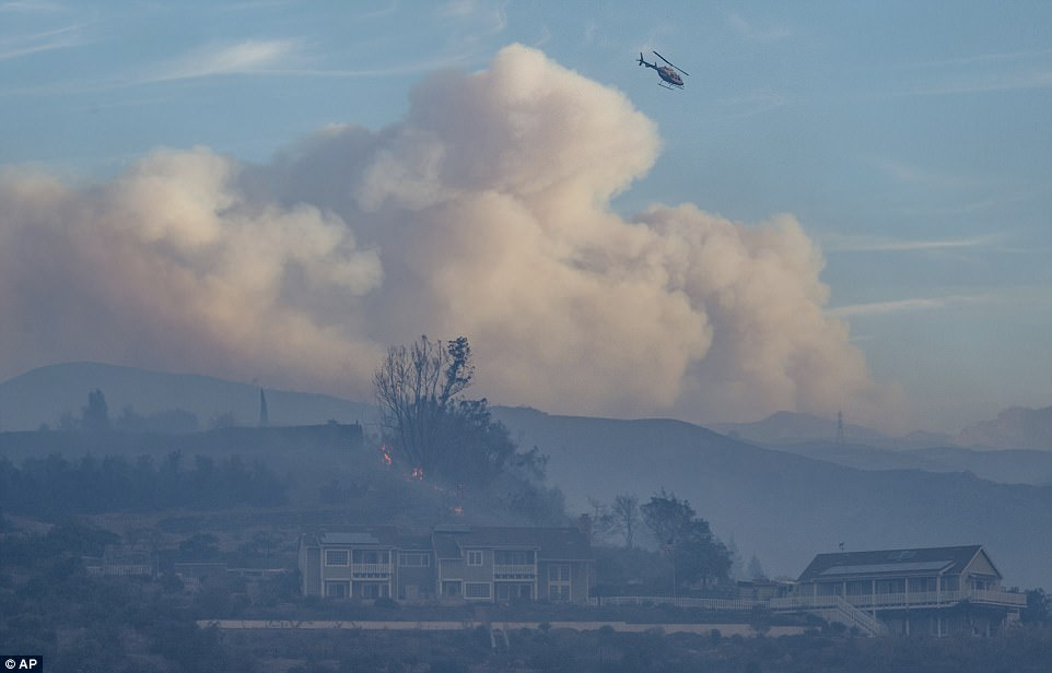 A helicopter flew over two homes as smoke clouds form in the distance after the wildfire swept through the Shepard Mesa neighborhood in Carpinteria, California