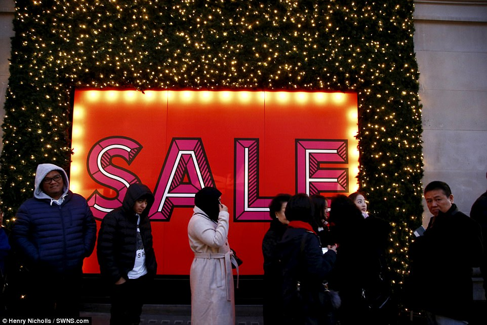 On London's Oxford Street tourists are pictured queuing for the Next Boxing Day Sale. Foreign visitors are expected to be among the biggest spenders, with some splashing out over £1,000 each